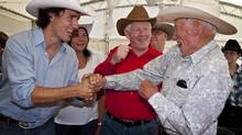Liberal leader Bob Rae, centre, and MP Justin Trudeau, left, joke with Lyall Curry, 92, while attending the party's annual Stampede breakfast in Calgary, Saturday, July 7, 2012. (Jeff McIntosh/CP)