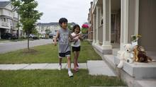 Diego and Camila Ruiz, 8 and 6, bring flowers to the Milton, Ont., home where a two-year-old boy died of heat stroke on Wednesday after spending considerable time in a very hot car. (Matthew Sherwood FOR THE GLOBE AND MAIL)