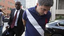 Adriano Furgiuele is brought in to RCMP headquarters in handcuffs on Aug. 9, 2012. Mr. Furgiuele is one of several Canada Revneue Agency oficials charged in a fraud crackdown called Project Cloche. (CHRISTINNE MUSCHI FOR THE GLOBE AND MAIL)