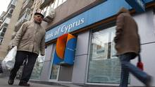 People walk past a branch of Bank of Cyprus in Bucharest March 25, 2013. (BOGDAN CRISTEL/REUTERS)