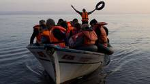 In this photo taken on Sept. 27, 2015, Syrian refugees arrive with others from Turkey on the shores of the Greek island of Lesbos, aboard a fishing boat. (Petros Giannakouris/AP)