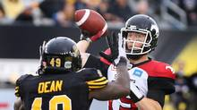 Calgary Stampeders quarterback Bo Levi Mitchell (19) passes as Hamilton Tiger-Cats' Larry Dean defends during the first-half of CFL football action in Hamilton on Saturday, October 1, 2016. (Peter Power/THE CANADIAN PRESS)