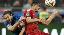 Toronto FC's Gilberto, right, heads the ball past Montreal Impact's Heath Pearce, left, during first half final Amway Canadian Championship soccer action in Toronto on Wednesday, May 28, 2014. (Nathan Denette/THE CANADIAN PRESS)