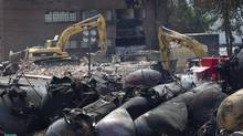 """Crews continue to dig through the rubble inside the """"red zone"""" in Lac-Mégantic, PQ on July 14, 2013. (Peter Power/The Globe and Mail)"""
