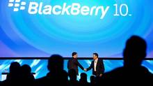 Andrew MacLeod, RIM managing director for Canada, left, and Brian Bidulka, chief financial officer, shake hands at the global launch of the new BB10 in Toronto. (NATHAN DENETTE/THE CANADIAN PRESS)