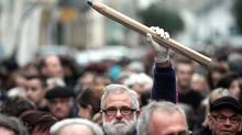 A man holds up a giant pencil during a gathering in Tarbes, southern France, on Jan. 8, 2015, in tribute to the 12 people killed the day before by two gunmen at the editorial office in Paris of French weekly satirical newspaper Charlie Hebdo. (LAURENT DARD/AFP/Getty Images)