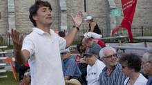 Liberal Party leader Justin Trudeau gestures as he talk to a group of concertgoers at the Festival de Musique Militaire in Quebec City on Aug. 21, 2013. (FRANCIS VACHON/THE CANADIAN PRESS)