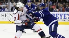 Toronto Maple Leafs defenceman Connor Carrick knocks Washington Capitals forward T.J. Oshie off of the puck in Toronto on Tuesday. (John E. Sokolowski/USA Today Sports)