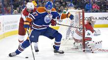 Carolina Hurricanes' Eric Staal (12) and Edmonton Oilers' Benoit Pouliot (67) battle for the puck as goalie Cam Ward (30) looks for the shot during second period NHL action in Edmonton, Alta., on Monday January 4, 2016. (JASON FRANSON/THE CANADIAN PRESS)