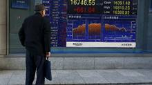 A man looks at an electronic board displaying the Nikkei average outside a brokerage in Tokyo, Japan, March 2, 2016. (Thomas Peter/Reuters)