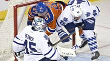 Toronto Maple Leafs' goalie Jonathan Bernier is crashed into by Edmonton Oilers' Connor McDavid and Roman Polak in Edmonton, Alta., on Thursday February 11, 2016. (JASON FRANSON/THE CANADIAN PRESS)