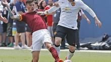 Manchester United's Wayne Rooney, right, and AS Roma's Alessio Romagnoli fight for control of the ball during an exhibition soccer match at Mile High Stadium in Denver. (Brennan Linsley/Associated Press)