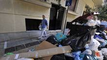 A woman walks past piles of garbage in Athens on October 14, 2011, on the eleventh day of a garbage collectors protest. Greece's two main unions said they would hold a two-day general strike next week against new austerity cuts by the government to address an unravelling debt crisis that has shaken the eurozone. (LOUISA GOULIAMAKI/AFP/Getty Images)
