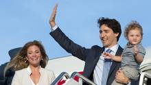Prime Minister Justin Trudeau, holding his son Hadrian, waves as he steps off the plane with his wife Sophie Gregoire-Trudeau during a welcome ceremony at Andrews Air Force Base, Md., on March 9, 2016. (Paul Chiasson/THE CANADIAN PRESS)