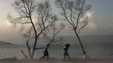 Two women, one of them carrying a baby on her back, walk next to Lake Azuei near the border with the Dominican Republic in Malpasse, Haiti, Tuesday, Aug. 9, 2011. (AP Photo/Ramon Espinosa) (Ramon Espinosa/Ramon Espinosa/AP)