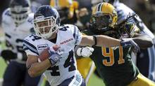 Toronto Argonauts' Chad Kackert (L) eludes the grasp of Edmonton Eskimos' Marcus Howard (R) during their CFL football game in Edmonton June 30, 2012. (DAN RIEDLHUBER/REUTERS)