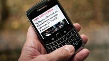 A Blackberry user in Montreal reads a story about a service outage that is affecting millions of users of the smartphone that spread to North America Oct. 12, 2011. (Paul Chiasson/The Canadian Press/Paul Chiasson/The Canadian Press)