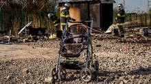 Firemen work next to a stroller near the remains of burnt huts on April 11, 2017 at the Grande-Synthe migrant camp outside the northern French city of Dunkirk after a huge blaze destroyed the camp late April 10, 2017. (PHILIPPE HUGUEN/AFP/Getty Images)