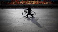 A man walks with his bicycle in front of a screen showing propaganda displays near the Great Hall of the People at Beijing's Tiananmen Square in this November 7, 2012 file photo. Rich Chinese are buying bicycles that cost more than the average citizen makes in three years, motivated by nostalgia for the days when two wheels were the primary means of transport. China is now the world's biggest auto market, but high-end bike sales are expected to grow by 10 per cent a year as they become a status symbol for wealthy executives. (CARLOS BARRIA/REUTERS)