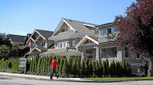 A man walks by a home in the Kitsilano neighbourhood of Vancouver, BC August 3, 2011. (Jeff Vinnick/THE GLOBE AND MAIL/Jeff Vinnick/THE GLOBE AND MAIL)