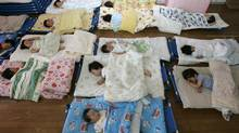 Nursery school children take a nap at Hinagiku nursery in Moriyama, western Japan, on May 27, 2008. (YURIKO NAKAO/REUTERS)
