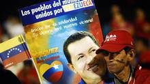 "A supporter of Venezuela's President Hugo Chavez holds a poster with a photograph of Chavez and the words ""The peoples of the world, united through Venezuela, thank you for your solidarity. Your victory will be ours"" while standing on a square in San Salvador, El Salvador, March 5, 2013. (Ulises Rodriguez/REUTERS)"