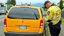 In this file photo, Constable Steve Shaw of the Vancouver Police Traffic Enforcement Unit writes a speeding ticket in 2008. (DARRYL DYCK/Darryl Dyck/CP Photo)