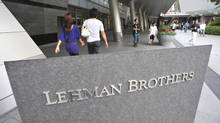 People stroll by a company sign of Lehman Brothers Holdings Inc. in front of a buiilding where its head office in Tokyo is housed Sept. 15, 2008 following the company's filing for bankruptcy protection in the United States. (Katsumi Kasahara/The Associated Press/Katsumi Kasahara/The Associated Press)