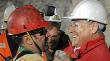 Chilean President Sebastian Pinera, right, hugs Mario Sepulveda after the miner was rescued from the collapsed San Jose gold and copper mine where he was trapped with 32 other miners for more than two months. (Jose Manuel de la Maza/AP/Jose Manuel de la Maza/AP)