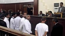 Al-Jazeera English bureau chief Mohamed Fahmy, center, stands in a courtroom during his trial in Cairo on March 31. (Sarah El Deeb/THE ASSOCIATED PRESS)
