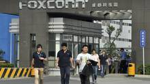 Workers walk out of the entrance to a Foxconn factory in Chengdu, Sichuan province July 4, 2012. (STRINGER/CHINA/REUTERS)