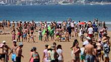 People gather on the beach in Loredo near Santander, on August 2, 2015. Spanish tourism is at record levels, with visitors flocking to beaches. But the country is no miracle economy. Its jobless rate, at 22 per cent, is more than twice the precrisis level. (CESAR MANSO/AFP/Getty Images)