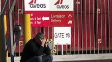 A laid off Aveo employee makes a call in front of the aircraft maintenance company's plant Tuesday, March 20, 2012 in Montreal.THE CANADIAN PRESS/Ryan Remiorz (Ryan Remiorz/RYAN REMIORZ/THE CANADIAN PRESS)