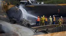 Crews work in the area of the derailed tanker cars in Lac-Mégantic, Que., on July 14, 2013. The Canadian Transportation Agency is reviewing how it determines the minimum insurance amounts for railways after the disastrous crash. (Peter Power/The Globe and Mail)