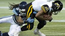Hamilton Tiger-Cats quarterback Henry Burris is tackled by Toronto Argonauts linebacker Marcus Ball (Nathan Denette/The Canadian Press)
