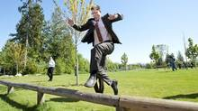 BC NDP Leader Adrian Dix jumps over a wooden fence as he returns to his bus following a provincial election campaign stop at Chimney Heights Park in Surrey, B.C. on Monday, May 6, 2013. (Justin Tang/THE CANADIAN PRESS)