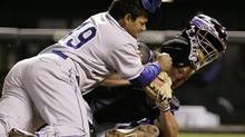 In this Sept. 27, 2006, file photo, Los Angeles Dodgers' Delwyn Young, left, is out at home plate as he collides with Colorado Rockies catcher JD Closser during the seventh inning of a baseball game in Denver. (Jack Dempsey/AP)