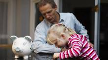 Financial adviser Arpad Komjathy helps his five-year-old daughter Anna count money. Mr. Komjathy is building on what Anna is learning at senior kindergarten about coins and paper money. (Michelle Siu for The Globe and Mail)