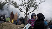 A woman hold her child as migrants and refugees wait to be allowed to cross the Macedonian borders, near the northern Greek village of Idomeni, Friday, Dec. 4, 2015. (Petros Giannakouris/AP)