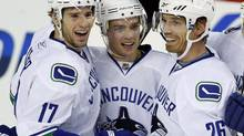 Vancouver Canucks' Mason Raymond, centre, celebrates his second goal with teammates Ryan Kesler, left, and Mikael Samuelsson, from Sweden, during first period NHL hockey action against the Vancouver Canucks in Calgary, Sunday, Dec. 27, 2009. The Vancouver Canucks have avoided arbitration with Mason Raymond by signing the forward to a two-year, US$5.1 million contract. (Jeff McIntosh/THE CANADIAN PRESS)