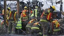 Firefighters rake at the site of the Résidence du Havre in L'Isle-Verte, Que., Jan. 28, 2014. Canadian investigators sifted painstakingly through the charred ruins of a Quebec seniors' residence, seeking clues on what caused a massive blaze last week that authorities fear killed 32 people. (MATHIEU BELANGER/Reuters)