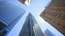 Skyscrapers that are home to big Canadian banks hover over a Bay Street intersection in Toronto. New CEOs, and a slowdown in the retail side of business, are likely to spur deals in the financial sector. (Gloria Nieto/The Globe and Mail)