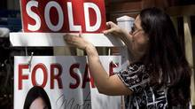 """A real estate agent puts up a """"sold"""" sign in front of a house in Toronto on April 20, 2010. (Darren Calabrese/THE CANADIAN PRESS)"""