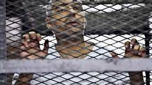 Mohammed Fahmy appears in a defendant's cage at a courtroom in Cairo in May 2014 (Hamada Elrasam/AP)