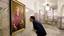 A government worker examines a painting of former Alberta premier Alison Redford hanging in the Alberta Legislature in Edmonton on Sept. 8, 2016. (JASON FRANSON/THE CANADIAN PRESS)