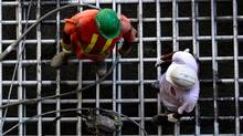 Workers stand on the foundation at a condominium construction project in Toronto. (Brent Lewin/Bloomberg)