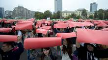 Protesters raise coloured papers during a protest against a gold mining project in front of the government headquarters in, Bucharest, Romania, Sunday, Oct. 13, 2013. (Vadim Ghirda/AP)