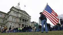 A protester holds an American flag at a rally on the State Capitol grounds in Lansing, Mich., Tuesday, Dec. 11, 2012. The crowd is protesting right-to-work legislation passed last week. Michigan could become the 24th state with a right-to-work law next week. (Paul Sancya/AP)