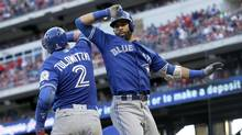 Troy Tulowitzki and Jose Bautista celebrate Bautista's three-run home run against the Texas Rangers during the ninth inning of Game 1. (LM Otero/The Associated Press)