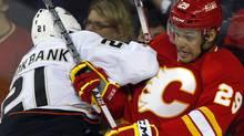 Anaheim Ducks' Sheldon Brookbank, left, checks Calgary Flames' Akim Aliu, from Nigeria, during third period NHL hockey action in Calgary, Alta., Saturday, April 7, 2012. The Calgary Flames beat the Anaheim Ducks 5-2. THE CANADIAN PRESS/Jeff McIntosh (Jeff McIntosh/CP)